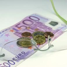Brille auf Geldschein mit Münzen
